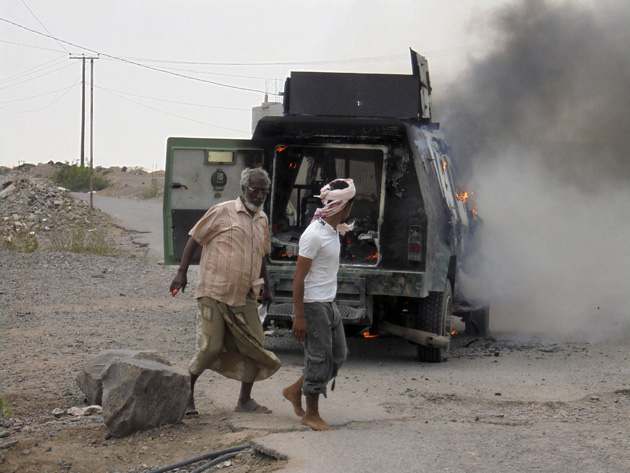 People walk by a police APC attacked by militants in Lahej near Aden