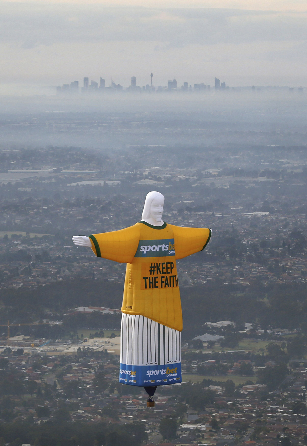 A hot air balloon in the shape of Brazil's Christ the Redeemer statue flies over the Sydney skyline