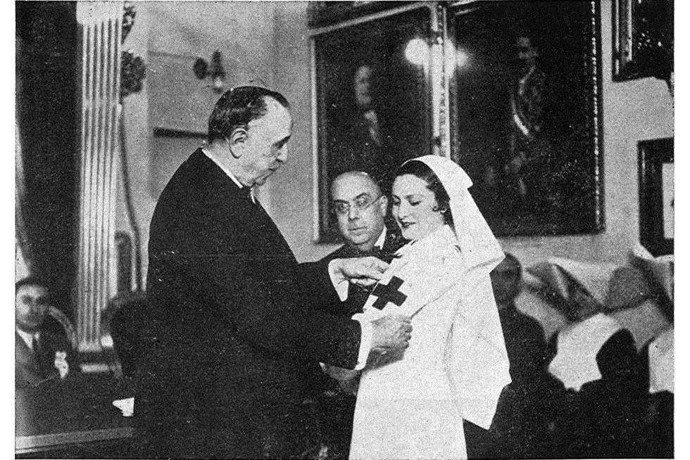 """El que fuera presidente de Cruz Roja en 1936, Ángel Guirao, coloca un brazalete a una nueva """"dama enfermera""""."""