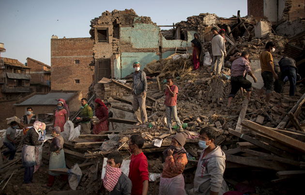 Residents clear debris as they look for their belongings from collapsed houses following Saturday's earthquake in Bhaktapur