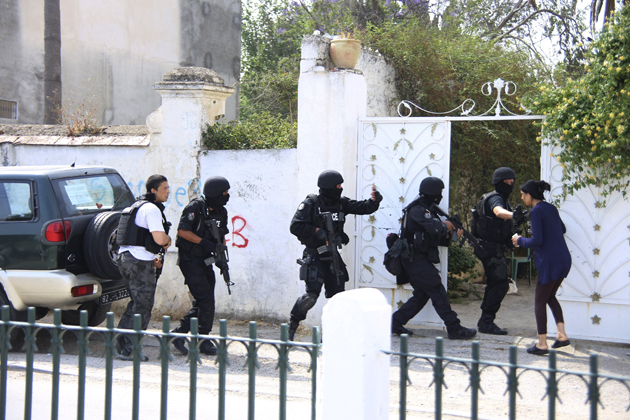 Tunisian anti-terrorism brigade personnel enter a house to take position after a shooting at the Bouchoucha military base in Tunis