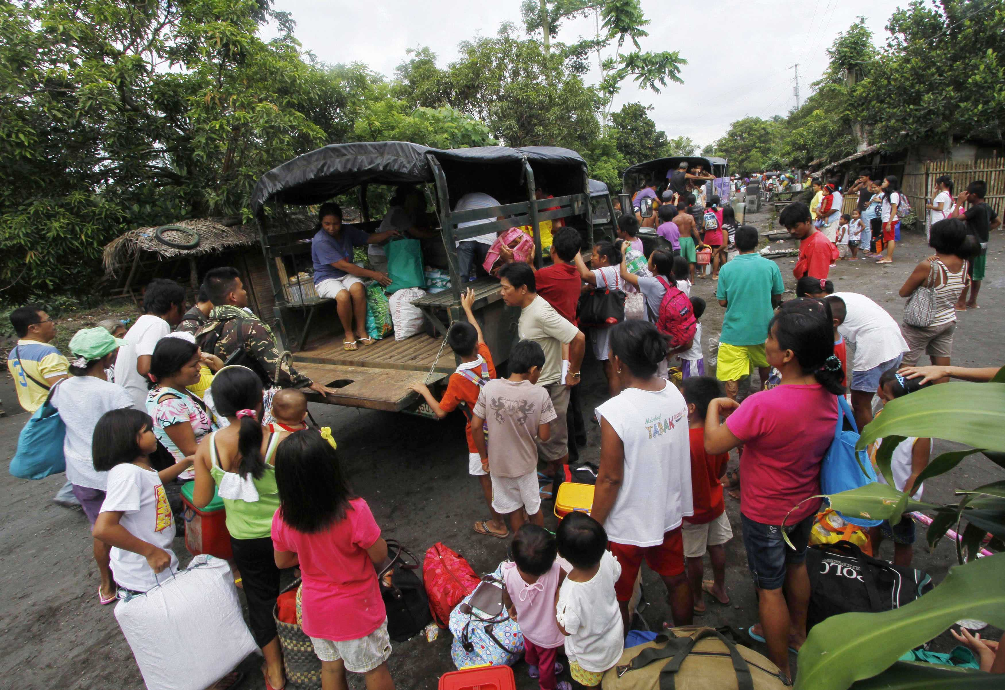 Residents with their belongings board a military truck as they evacuate their homes after the Mayon volcano spewed smoke in Albay province, Bicol region, south of Manila