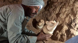 Un experto trabaja en el interior de una de las tumbas halladas en el templo del faraón Amenhotep II con un vaso canopo en sus manos usado por los antiguos egipcios para guardar las vísceras del fallecido embalsamadas