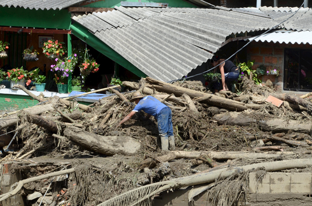 A man clears rubble from the ruins of his house, after a landslide sent mud and water crashing onto homes in the municipality of Salgar