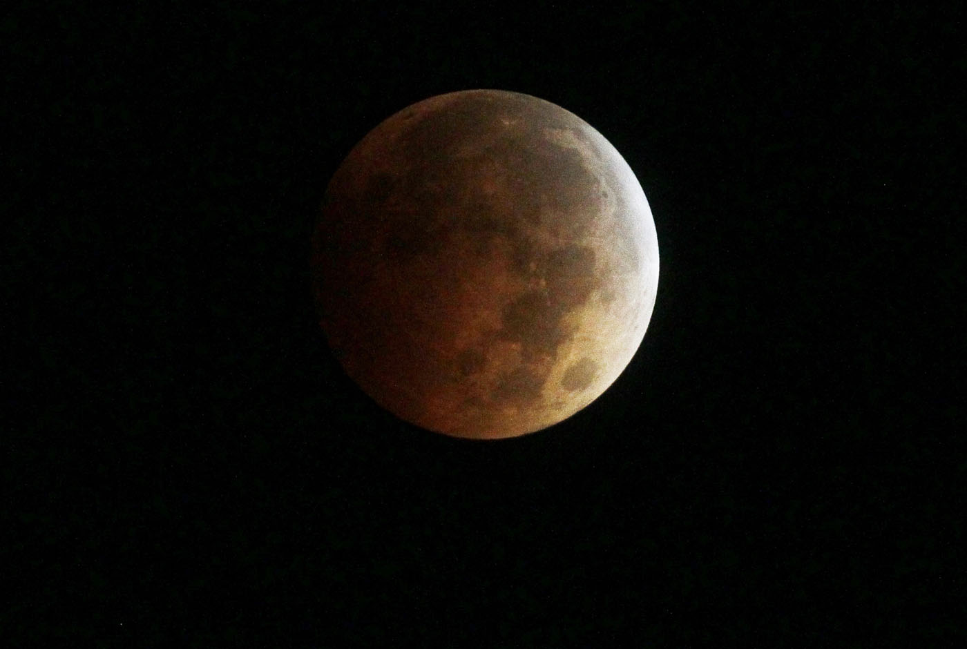 The moon turns orange during a total lunar eclipse as seen from Golden